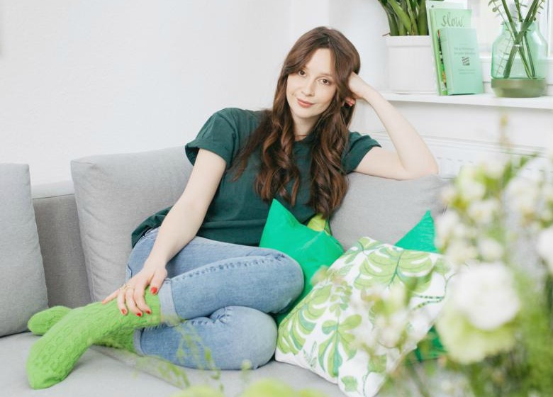 Young woman wearing green socks in her trendy flat with green accessories