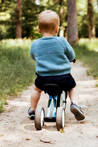 Kleiner Junge auf Dreirad in Strickjacke in blau